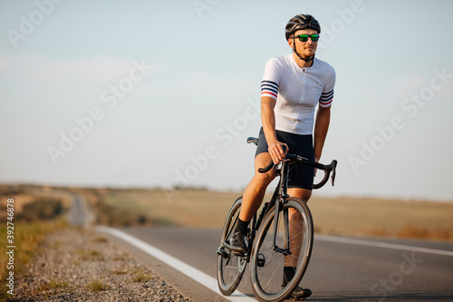 Tela Strong athlete standing at countryside with black bike