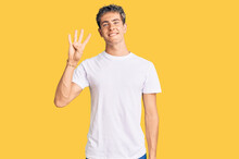 Young Handsome Man Wearing Casual White Tshirt Showing And Pointing Up With Fingers Number Four While Smiling Confident And Happy.