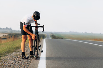 Male athlete in protective helmet checking wheels on bike