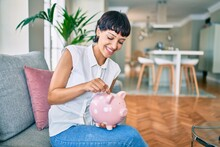 Young Brunette Woman Smiling Happy Putting Money Savings Inside Of Piggy Bank