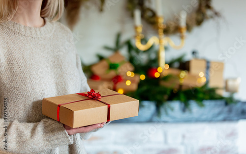 Foto Woman hold gift box near Christmas decorated fireplace at home