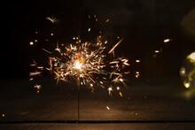Burning Sparkler On A Dark Wooden Background