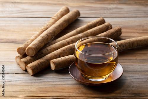 Stampa su Tela Burdock tea on a wooden board in the background