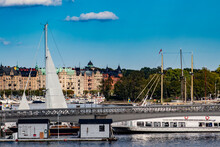 Sailboats And Ships Cruise Along The Waters Across From The Royal Palace In The Gamla Stan Neighborhood Of Stockholm, Sweden