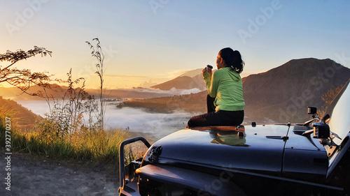 Woman sit on car hood while enjoy mount batur view