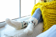 Beautiful Young Woman In Warm Socks And With Plaid Sitting On Window Sill, Closeup