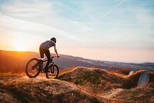 A Mountain Biker Riding A Bike Through The Hills