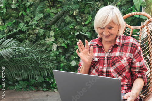 Surprised happy elderly woman waves to her companion in video chat Fotobehang