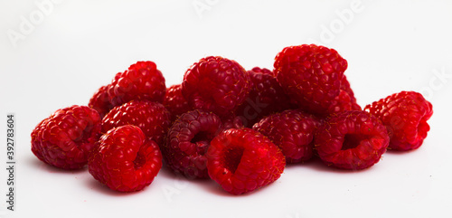 Close up of ripe red raspberries on white surface, nobody