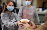 Volunteers serving hot soup for homeless in community charity donation center, coronavirus concept.