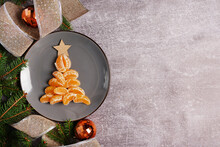 Christmas Decorations And Fir Tree Made From Tangerines On Plate, Gray Background With Copy Space