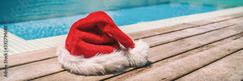 Photo Christmas background banner santa claus red hat on swimming pool vacation holiday resort horizontal header for south holidays winter vacations