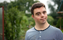 Portrait Of Down Syndrome Adult Man Standing Outdoors In Garden.