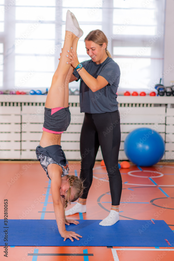 Fototapeta Physical activity for children, child doing a hand stand with trainer