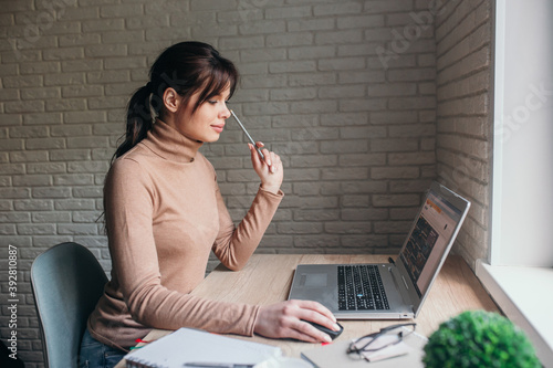 young woman wearing glasses using laptop computer working studying at home office