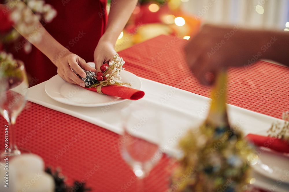 Fototapeta Close-up image of woman putting decorated napkin on table when preparing for Chrismas celebration at home