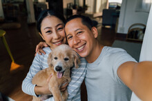 Young Adult Asian Couple Holding A Puppy Taking A Selfie From A Phone With Home Interior In Background. 30s Mature Man And Woman With Dog Pet Taking A Family Photo Shots. - Happy Group Portrait