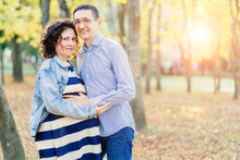Happy Young Parents, Mom And Dad, Hugging Baby Bump, Enjoying Beautiful Moment At Park. Young Family Or Couple Or Man And Pregnant Woman Walking Through Colorful Trees In Fall Or Autumn.
