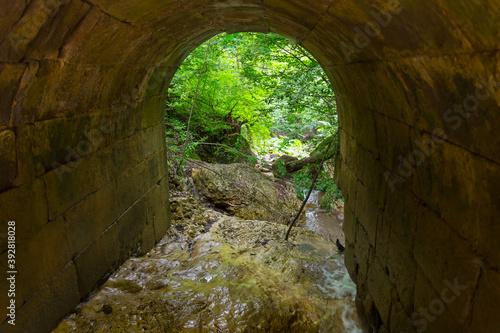 Papel de parede Arch of old stone bridge overthe mountain creek