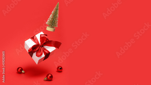 Fototapeta Holiday Christmas background. Golden winter tree, white gift box with red ribbon falling with balls and sparkling lights on reddish background for greeting card. Christmas, winter, new year concept. obraz