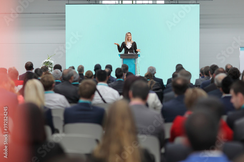 Fotografering Businesswoman speaking on a pedestal on a conference in front of an audience