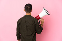 Young Caucasian Man Isolated On Pink Background Holding A Megaphone And In Back Position