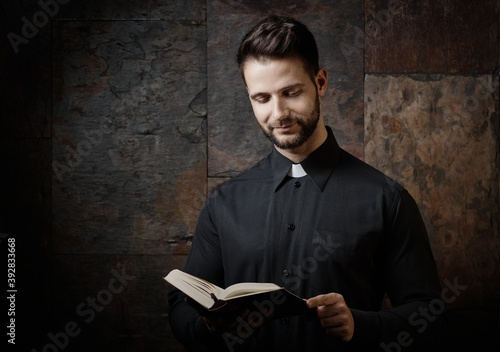 Obraz na plátně Portrait of handsome young catholic priest reading the prayer book against dark background