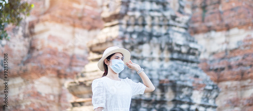 Obraz na plátně Tourist Woman in white dress wearing surgical face mask, protection COVID-19 pandemic during visiting in Wat Chaiwatthanaram temple in Ayutthaya