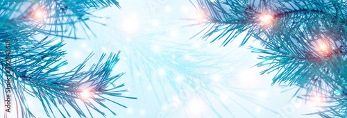 Blurred festive Christmas background. Pine branch close up, blurry bokeh lights, snowflakes.