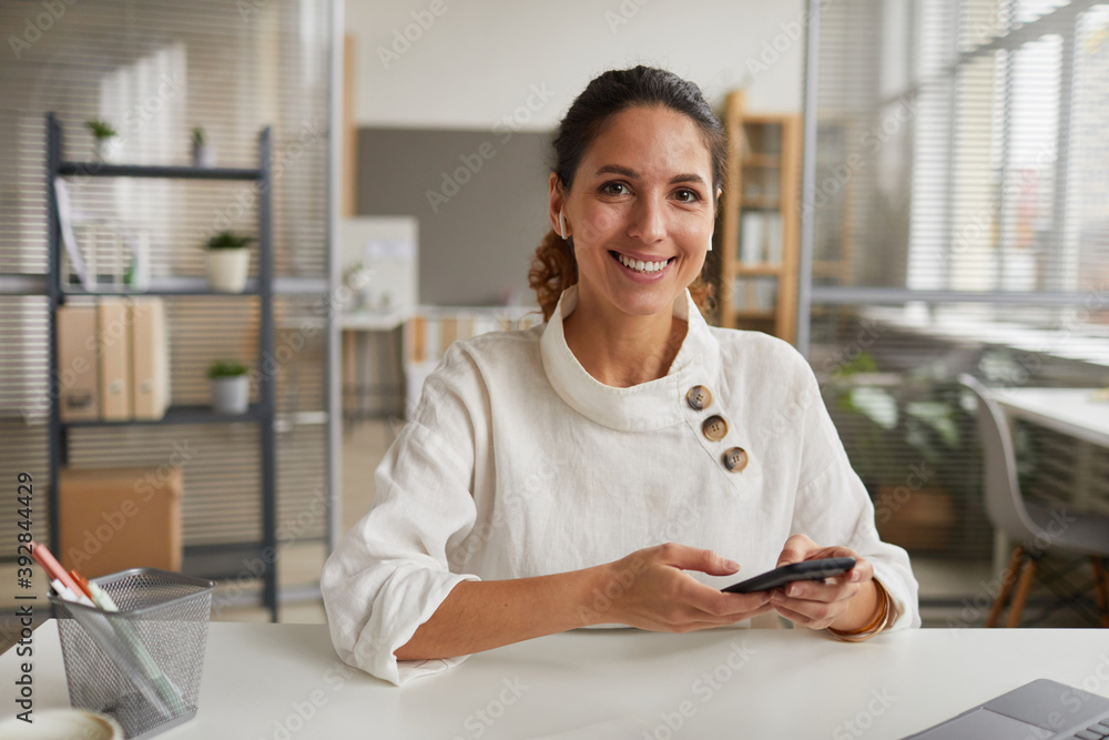 Fototapeta Portrait of smiling businesswoman holding smartphone and looking at camera while sitting at desk in office, copy space