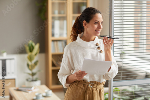Waist up portrait of smiling successful businesswoman recording voice message via smartphone while standing by window at workplace, copy space