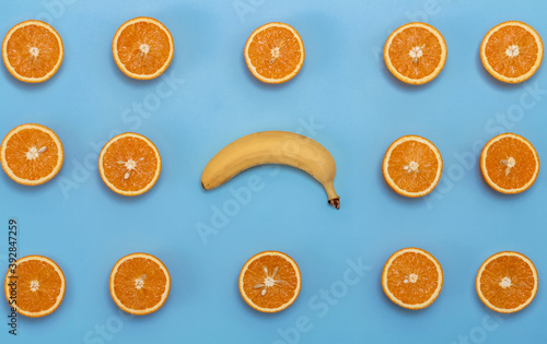oranges with a banana in the center on a blue background Fototapet