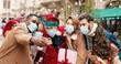 Leinwandbild Motiv Santa Claus in mask hugs African American and Caucasian young people while taking selfie photo on cellphone. Portrait of males ad females friends take pictures with Santa on snowy street. X-mas spirit