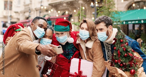 Fotografía Santa Claus in mask hugs African American and Caucasian young people while taking selfie photo on cellphone