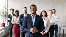 Successful African Businessman Standing With His Business Team In Office
