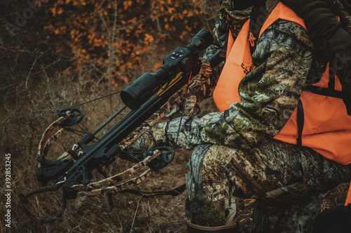 Foto Hunter holding a crossbow with a night vision scope, close-up, soft focus