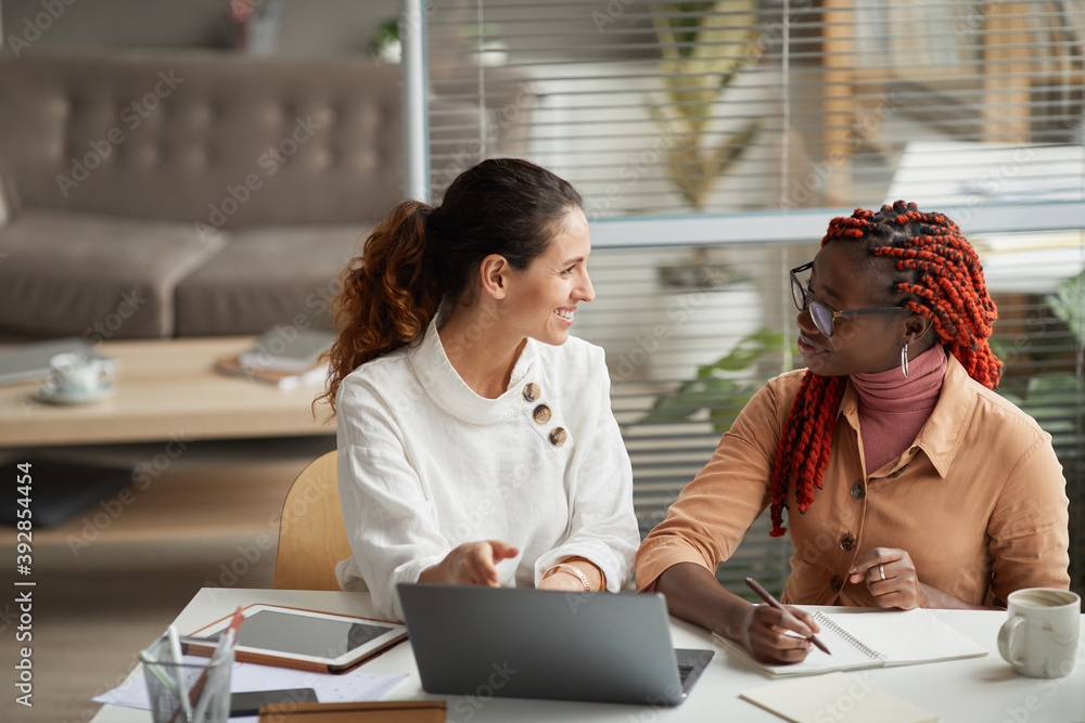 Fototapeta Portrait of two smiling businesswomen discussing project while sitting at desk together and working on startup in office, copy space