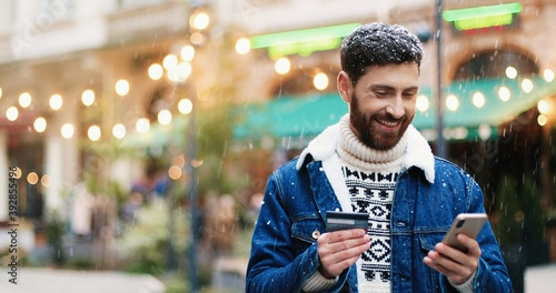 Leinwand Poster Handsome young joyful Caucasian man standing in city decorated with lights and texting on smartphone