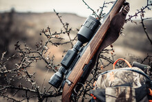 Hunting Rifle With A Scope Near A Backpack On A Background Of An Autumn Forest, Soft Focus