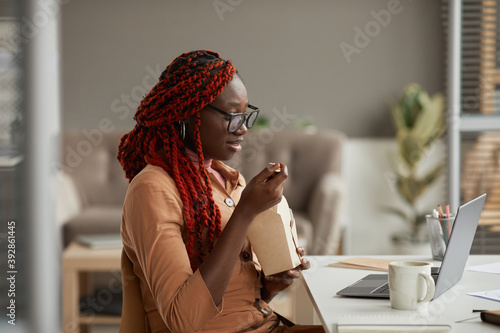 Obraz na plátně Side view portrait of young African-American woman eating takeout lunch and look