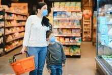 Authentic Shot Of Mother And Son Wearing Medical Masks To Protect Themselves From Disease Making Shopping For Groceries Together In Supermarket.
