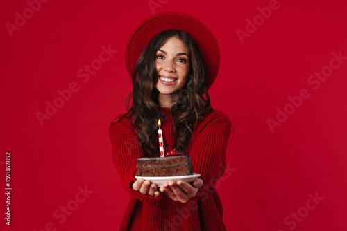 Cheerful beautiful brunette girl in hat showing birthday cake Wallpaper Mural