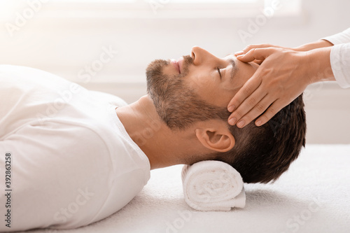 Cosmetologist making relaxing massage for handsome middle aged man