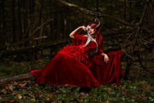 Maleficent Woman In Red Clothing And Horns In Dark Forest. Posing In Magik Forest