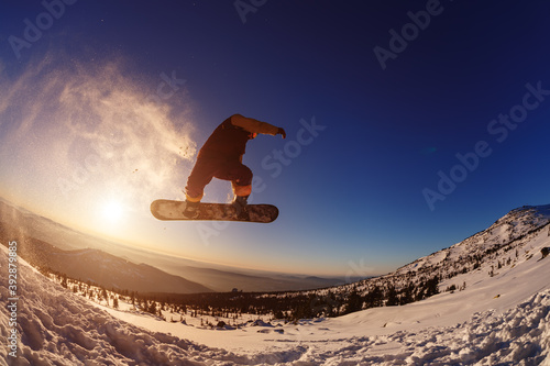 Papel de parede Snowboarder jumping against the sunset sky
