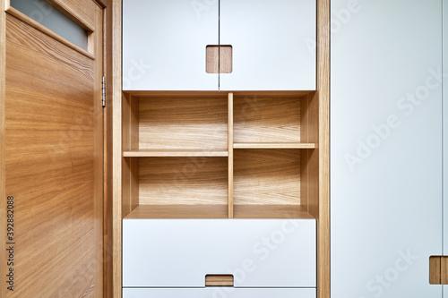 Obraz Modern wardrobe with finger pull design. Wooden wardrobe with light gray cabinet doors. Modern furniture - fototapety do salonu
