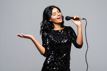 Portrait Of Happy Young Woman Singing With Microphone Isolated On Gray Background