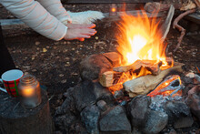 A Woman Warms Her Hands By The Fire In The Forest. Vacation Concept, Privacy. Late Evening