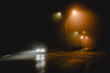one moving car in a foggy city road at night with headlights on