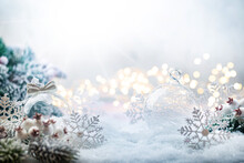 Christmas White Decorations On Snow With Fir Tree Branches And Christmas Lights. Winter Decoration Background